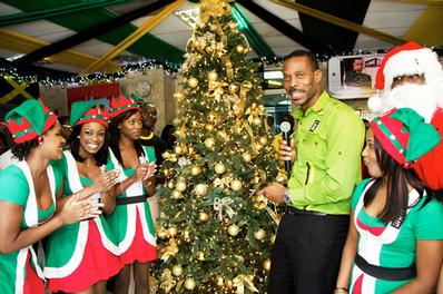 garry sinclair managing director of lime jamaica and cayman presses the button with assistance of santas helpers and lights up the christmas tree at